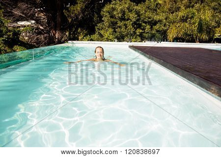 Smiling blonde swimming in the pool in a sunny day