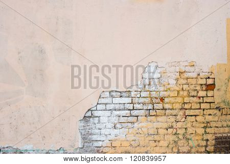 Old brick wall half weathered half covered with plaster. Obsolete background. Dirty wallpaper