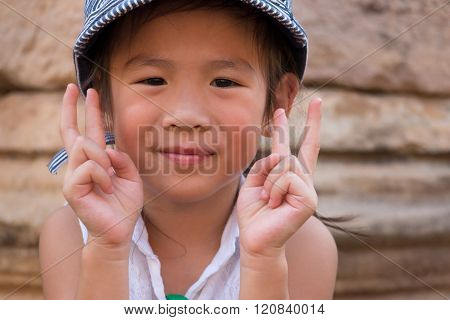 Little Girl Showing Two Hands With Victory Sign.