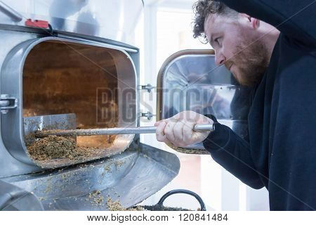 Man Taking Out Dried Malt From Furnace