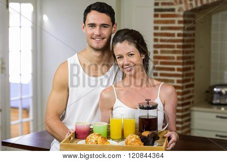 Portrait of happy couple standing together in kitchen with breakfast tray on tray