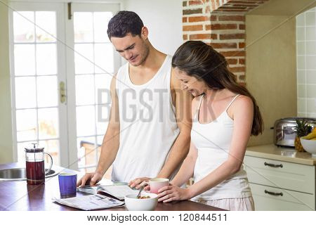 Young couple looking their personal organizer while having breakfast in kitchen