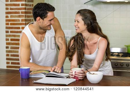 Young couple looking at each other while standing near kitchen worktop