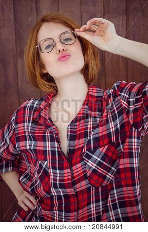 beautiful hipster woman wearing glasses and pouting at the camera on a wooden background