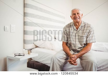 Portrait of senior man sitting on bed and smiling in bedroom