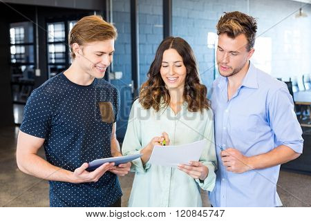 Three confident colleagues discussing in office with documents and tablet