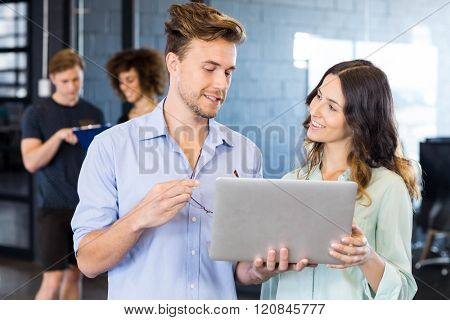 Two colleagues discussing in office on laptop while other two discussing behind them