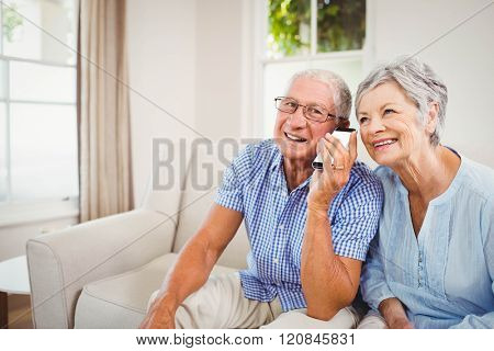 Senior couple smiling while talking on mobile phone