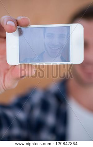 Handsome hipster taking selfie on wooden background
