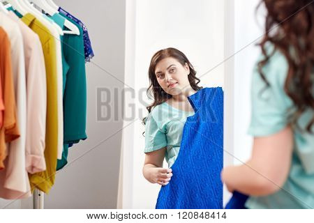 clothing, wardrobe, fashion, style and people concept - happy plus size woman with dress on hanger at mirror at home