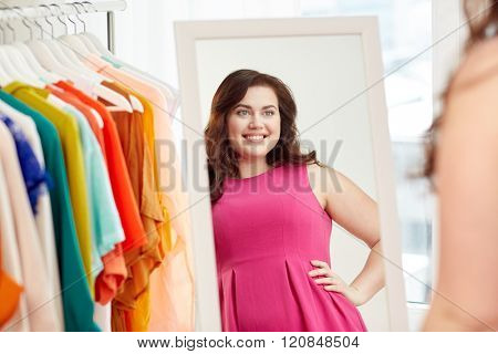 clothing, wardrobe, fashion, style and people concept - happy plus size woman posing at mirror at home