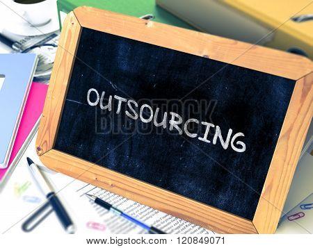 Outsourcing Handwritten by White Chalk on a Blackboard.