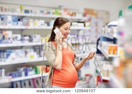 pregnancy, medicine, pharmaceutics, health care and people concept - happy pregnant woman calling on smartphone and choosing medication at pharmacy