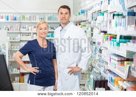 Confident Pharmacist And Assistant Standing With Hands On Hip