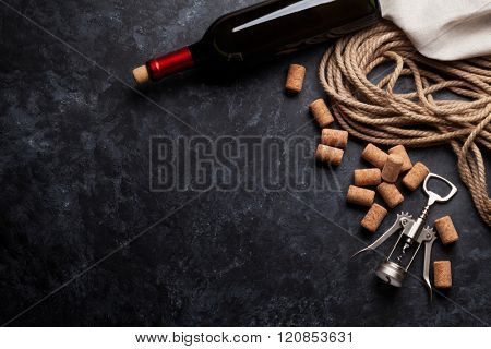 Wine, corks and corkscrew over dark stone background. Top view with copy space