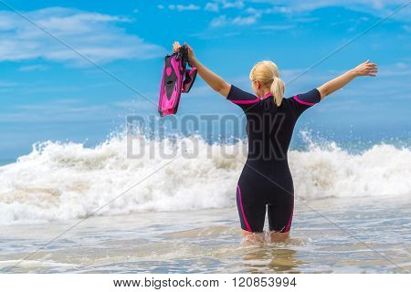 Woman Holding Mask And Flippers For Swimming On The Background The Wave