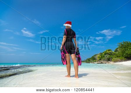 Woman Holding Mask And Flippers For Swimming In Santa Hat On The Beach
