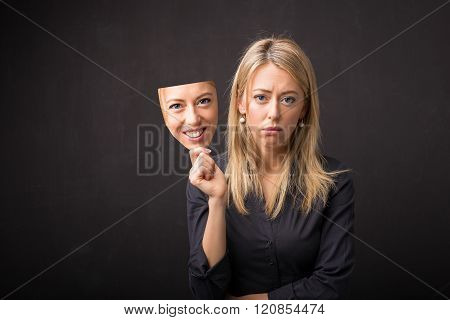 Woman holding mask of her happy face