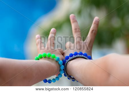 Two children showing a victory sign with red bracelets on her wrist