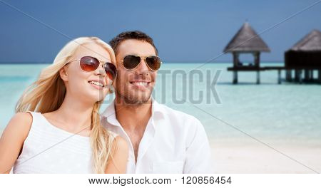summer holidays, tourism, vacation, travel and dating concept - happy couple in shades at sea side over beach with bungalow background