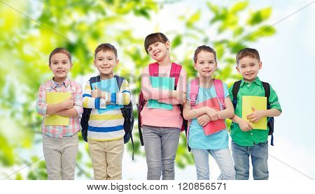 childhood, preschool education, learning and people concept - group of happy smiling little children with school bags and notebooks over summer green natural background