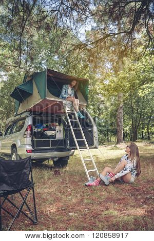 Woman in tent over car and other putting hiking boots