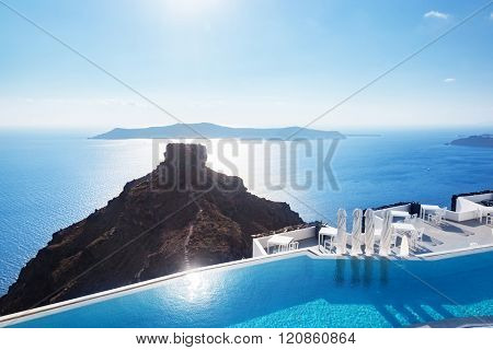 Swimming pool with a view on Caldera over Aegean sea, Santorini, Greece at hot sunny summer day.