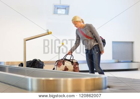 Female traveller collecting luggage at airport terminal.