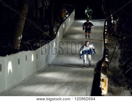 Three Sportsmen Skate Downhill