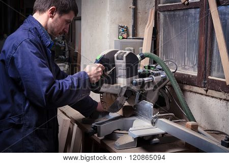 Portrait of carpenter man using circular saw in his workshop