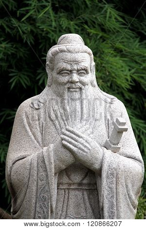 Chinese Statue Of Confucius With Bamboo Leaves Background