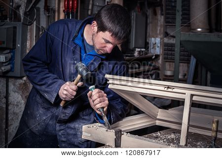 Carpenter Using Hammer And Chisel In Workshop