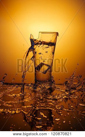 Exploding Glass cup with water shattering over orange background, crash and splashes