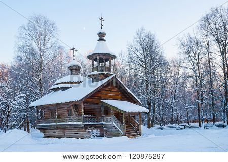 Wooden chapel in snowy winter forest at sunset