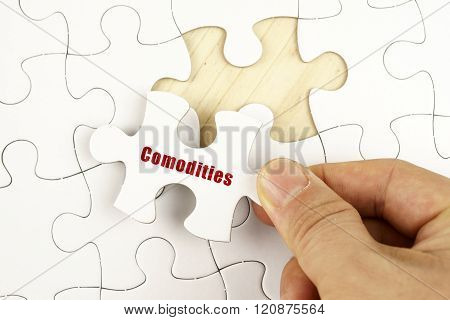 Finance Concept. Hand Holding Piece Of Jigsaw Puzzle Showing Comodities Word.