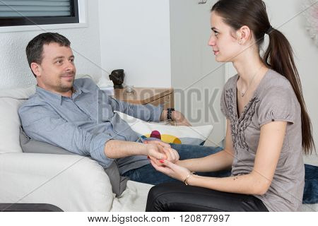 Man Having A Conversation With His Psychotherapist On Couch In Office.