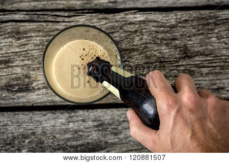 Top View Of Male Hand Pouring Dark Beer In A Glass