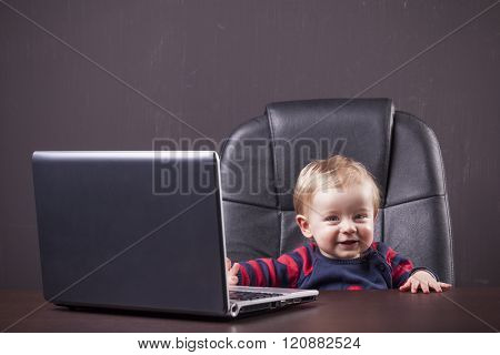 Smiling little boy playing with a laptop against grunge background