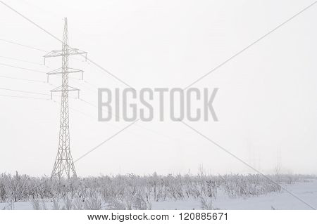 Post High-voltage Power Lines In The Fog In Winter