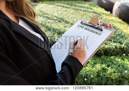 Businesswoman signing a life insurance policy on the street.
