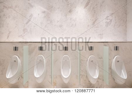 Row Of Five Urinals With Infrared Sensor, On Marble Wall, In Men's Public Toilet