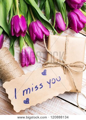 words I MISS YOU and bouquet of tulips