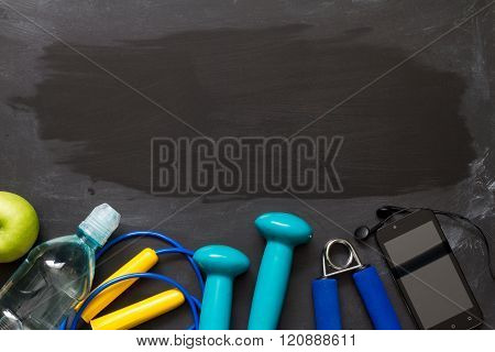 Fitness and sports gear on blackboard abstract background