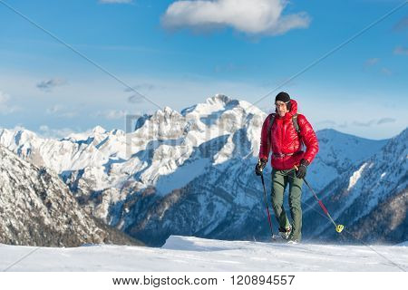 The man in snowshoes and with trekking poles  In the high mountains  in solitude