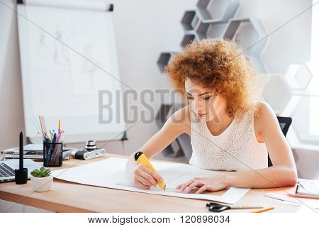 Beautiful focused young woman photographer cuttung sheet of paper using stationery knife and ruler on her workplace