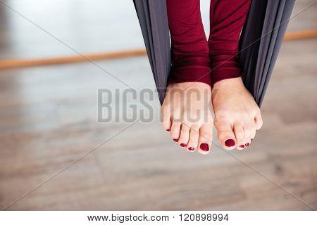 Closeup of legs of woman on hammock doing aerial yoga