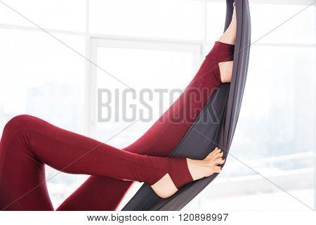 Closeup of beautiful legs of young woman in leggins using hammock in studio