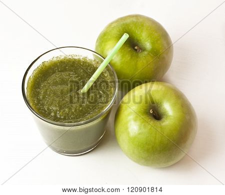 A glass of apple smoothie with a drinking straw and two apples, on white background