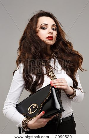 Young fashion woman in white jacket with handbag.