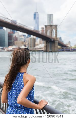 Woman looking at Brooklyn bridge and New York skyline on summer travel in NYC, USA. Unrecognizable tourist person view from behind looking away at skyscrapers.